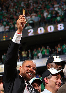 Doc Rivers holds a cigar aloft for the late red Auerbach